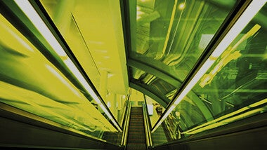 Escalator in neon yellow lights image banner for supply chain jobs