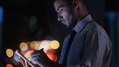 guy with a tablet at night image banner for contact us page